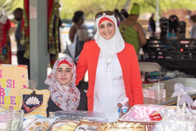 Dawlat Alrifai (right) sells baked goods at a Phoenix market as part of the Syrian Sweets Exchange bakers group.