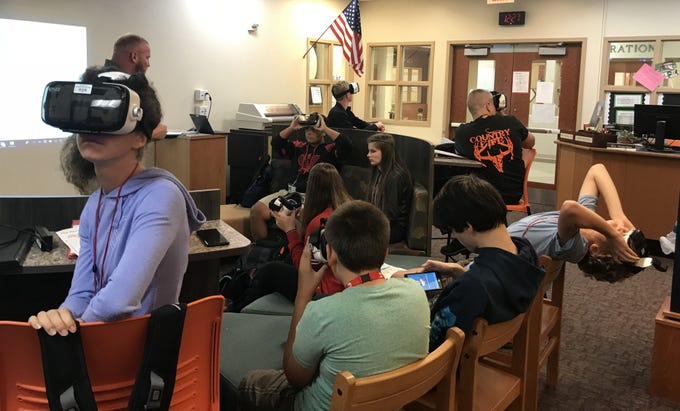 Students at Annville-Cleona High School use virtual reality goggles to learn about the earth, sun and moon. The image in the goggles changes as students move their heads in different directions.