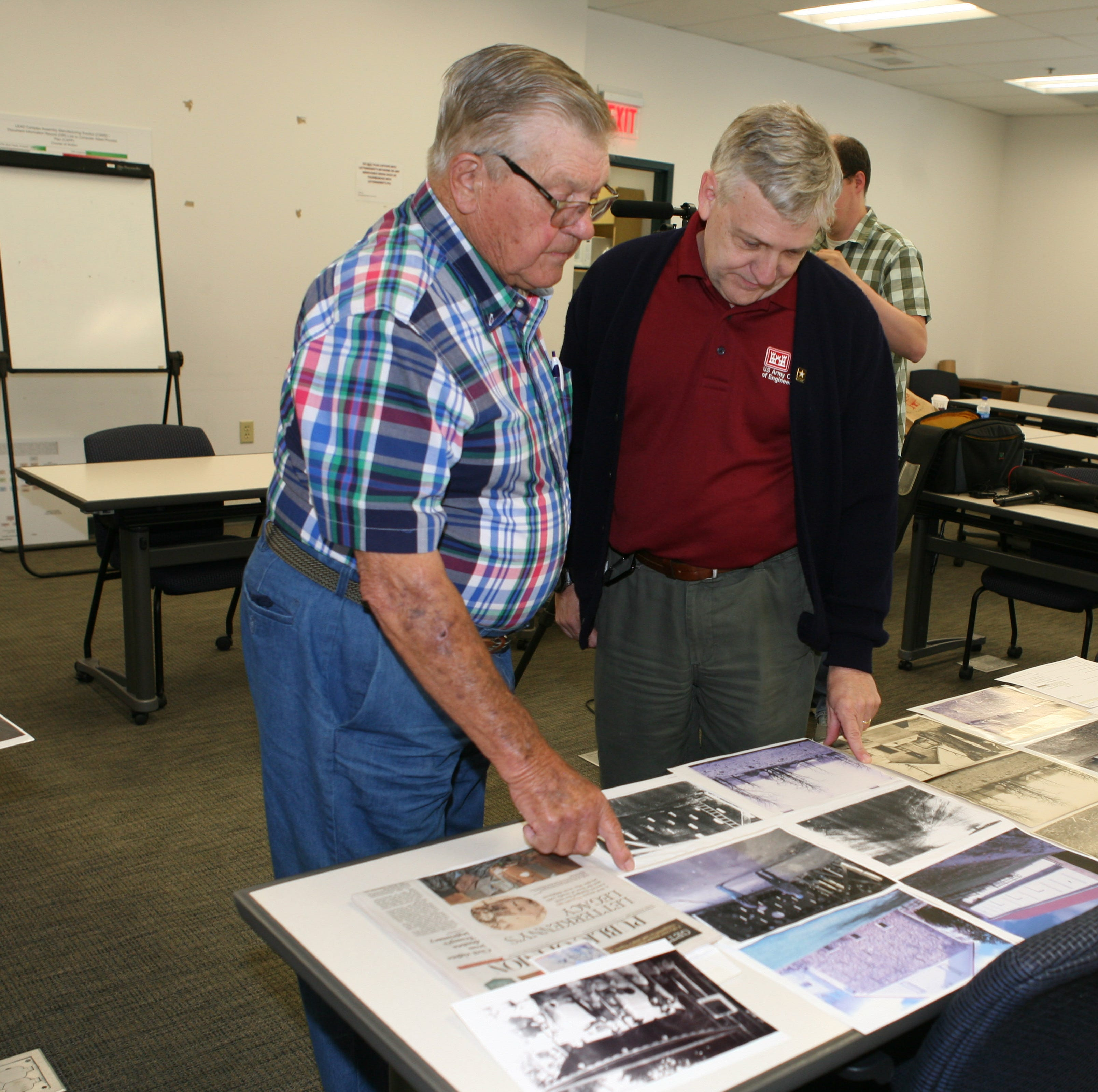 Dr. Douglas Warnock, acting president of the Letterkenny Army Depot Historical Committee,  looks at old photos with Harold Forrester as they discussed Forrester's life when his family lived on the land now home to the army depot.