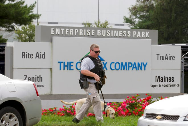 """ATF police officer with a sniffing dog walks out the industrial complex in Harford County, Md., Thursday, Sept. 20, 2018.   Authorities say multiple people have been shot in northeast Maryland in what the FBI is describing as an """"active shooter situation.""""  (AP Photo/Jose Luis Magana)"""