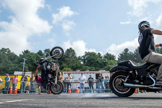 Joey Robinson does a one-handed wheely during the Ives Brothers stunt show at Harley-Davidson on Thursday. Motorcycle enthusiasts flooded into Harley-Davidson to tour the production plant, see the newest models of bikes and watch stunt shows, leading up to the 24th annual York Bike Night on Saturday downtown.