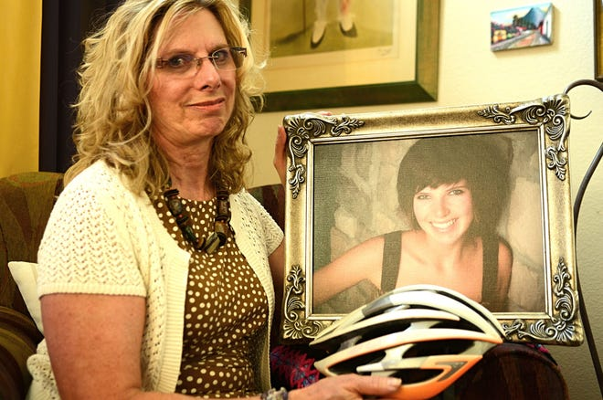 Trisha Greif holds a bicycle helmet and a framed photo of her then 23-year-old daughter, Erica Greif, who was killed in a head-on crash in April 2015. Erica Greif, a well-known Reno cyclist, will be honored at a dedication on Sept. 22, 2018.