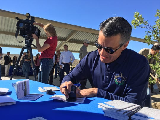 Gov. Brian Sandoval stamps a Nevada State Parks passport during the opening ceremony for the Walker River State Recreation Area on Sept. 19, 2018.