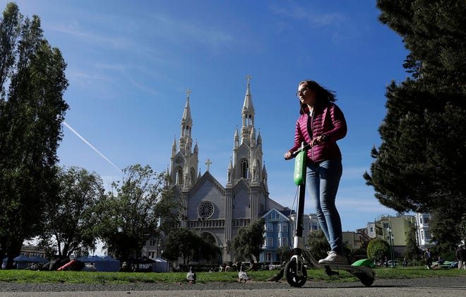In this April 17, 2018 file photo, a woman rides a motorized scooter in Washington Square Park in San Francisco. Gov. Jerry Brown signed legislation Wednesday, Sept. 19, 2018, requiring helmets only for people under age 18 while riding motorized scooters.