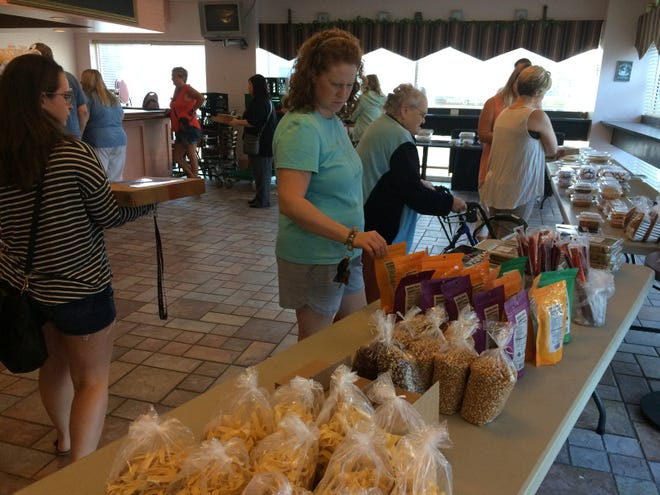 Customers look at goodies for sale Thursday during Rise 'n Roll Bakery's popup market at Leland Legacy.
