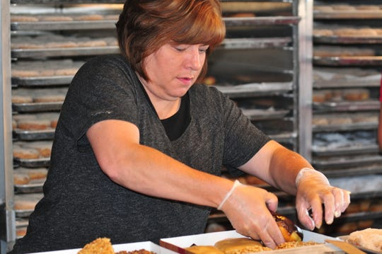 Angie Cross prepares a box of doughnuts for a customer Thursday during Rise 'n Roll Bakery's popup market at Leland Legacy.