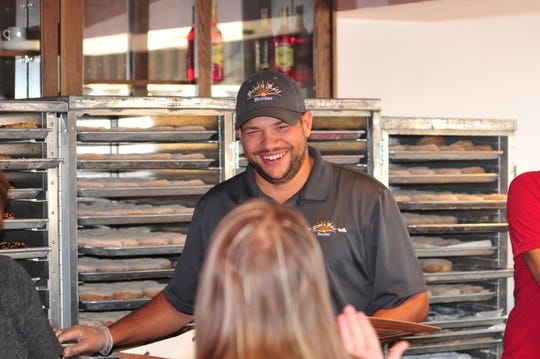 JC Price fills a box of doughnuts for a customer Thursday during Rise 'n Roll Bakery's popup market at Leland Legacy.