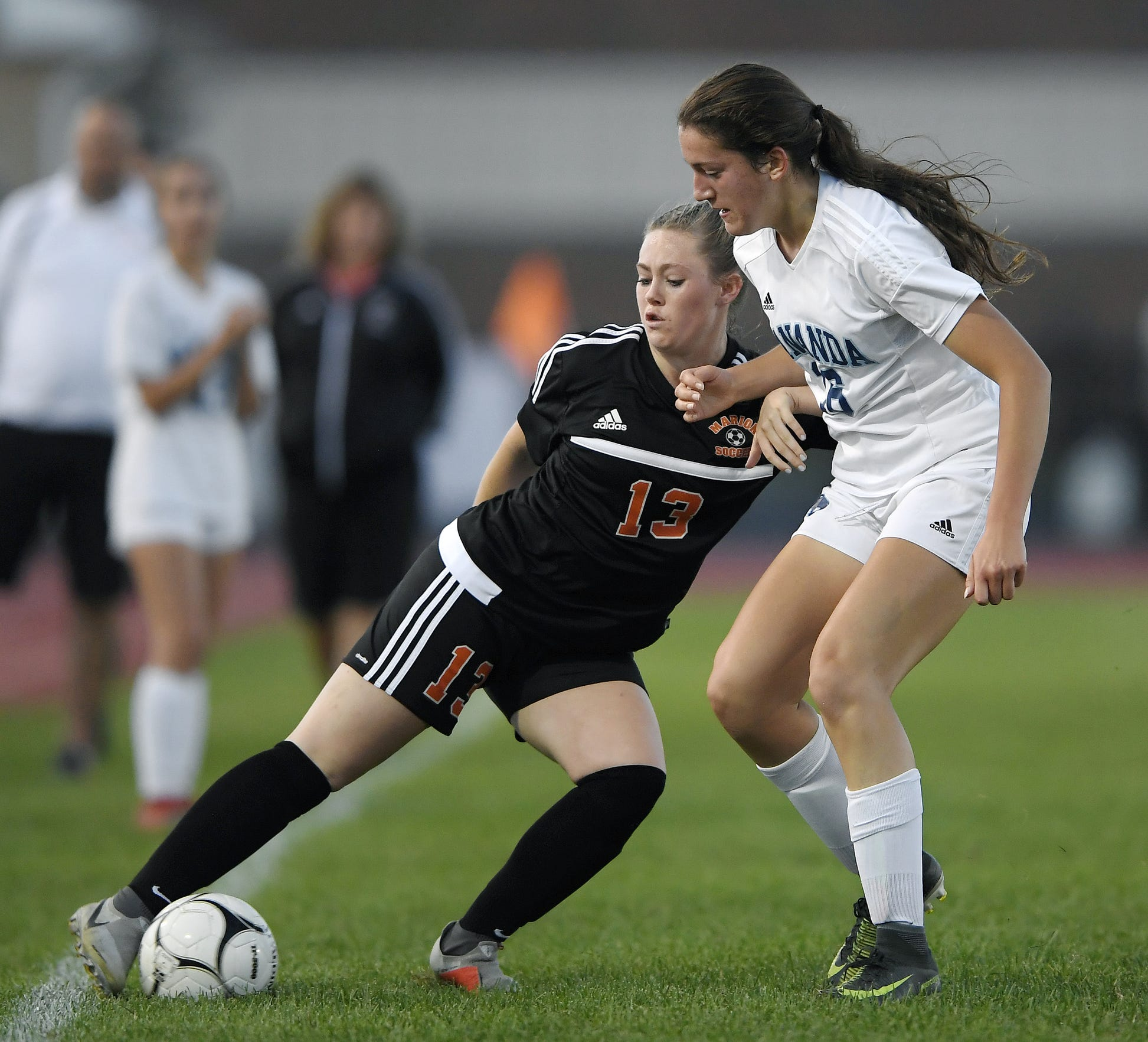 Marion's Chloe DeLyser, left, keeps the ball in play while defended by Gananda's Natalie McLoud.