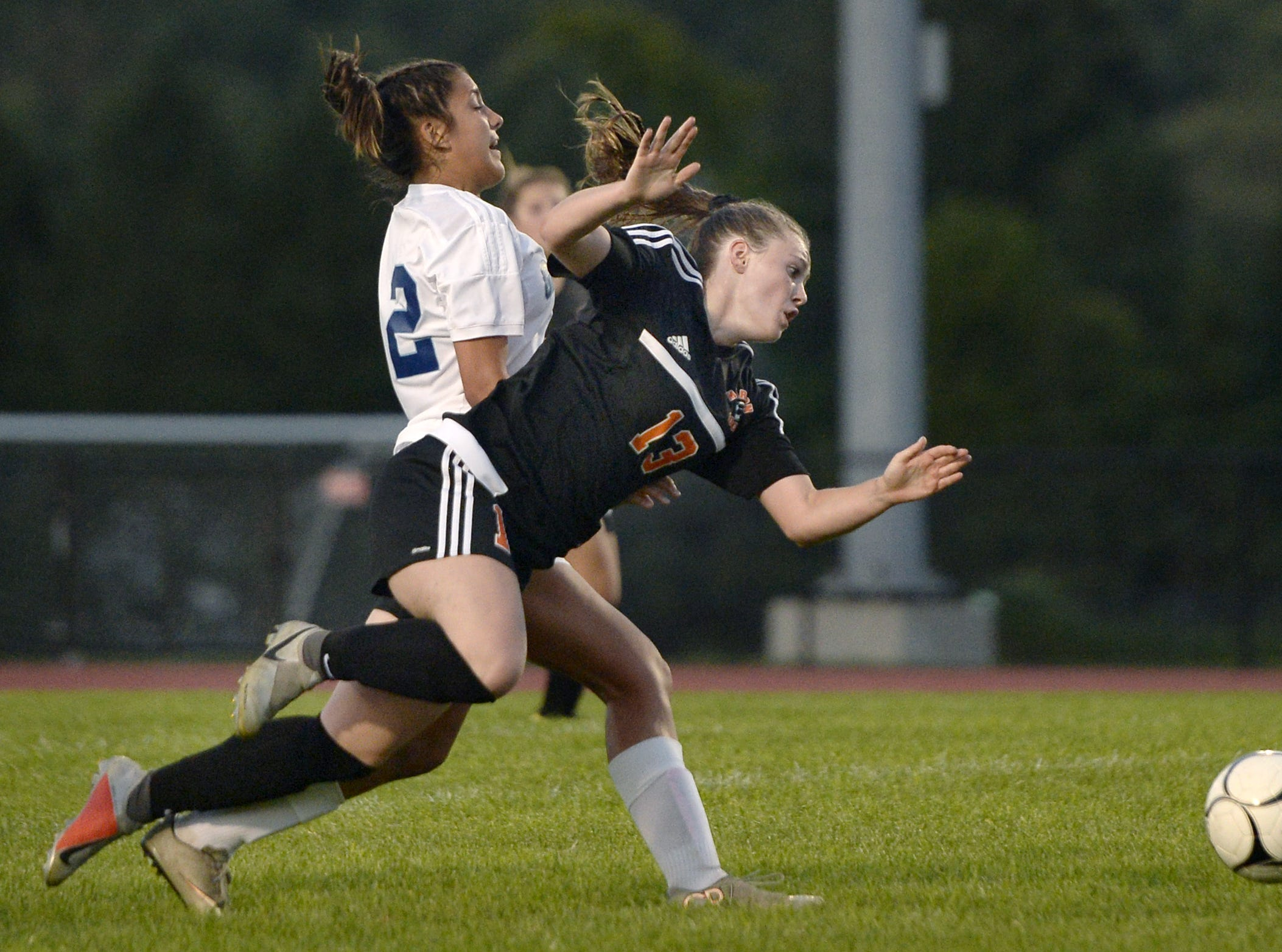 Marion's Chloe DeLyser, front, draws a foul against Gananda's Shelby Bryant leading to a Marion penalty kick.