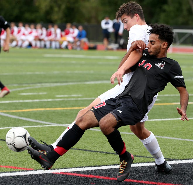 Hilton's Hussian Ali (10) and Fairport's Brandon Manz battle for the ball  in the first half of a Monroe County boys soccer game at Hilton Thursday.