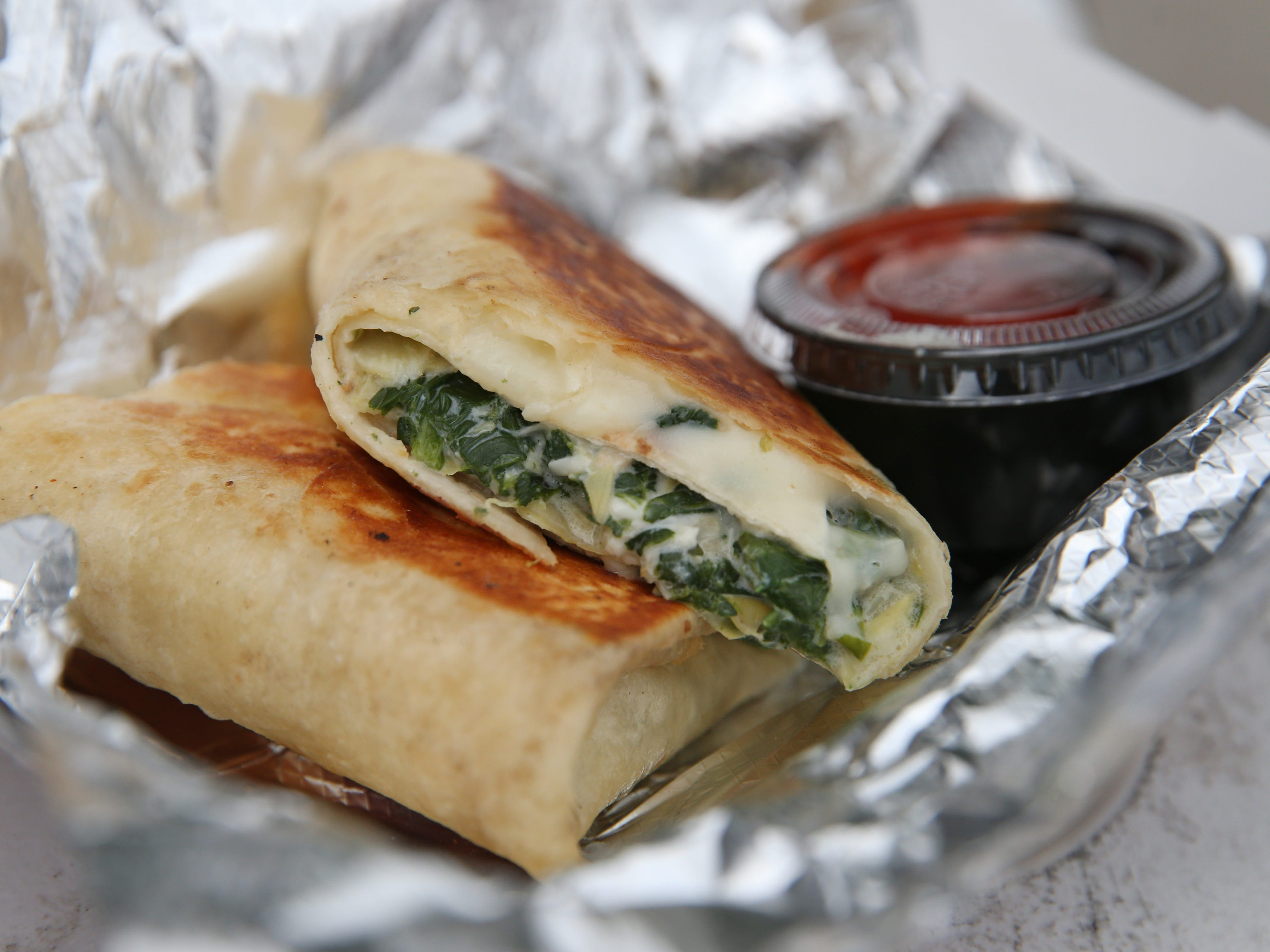 The Spin Art Burrito, spinach and artichoke dip wrapped in a tortilla and cooked until golden, is served from the Twist This food truck.