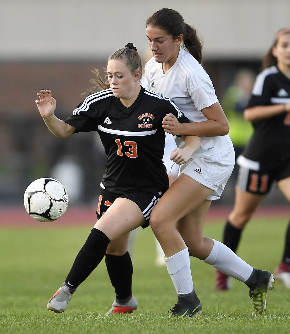 Marion's Chloe DeLyser, left, shields the ball from Gananda's Natalie McLoud during a game this season. DeLyser scored 79 goals this fall and holds the state record with 260 goals with one season left to play.