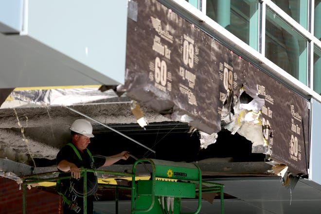 A Salem Health facilities employee works on a skybridge at Salem Health that was damaged after truck ran into it on Thursday, Sep. 20, 2018. The damage was determined cosmetic only, so the skybridge is still open to walk across.