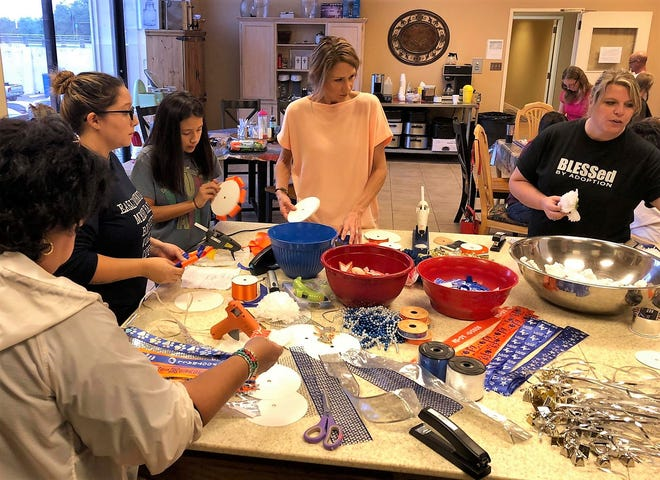 """A group gathers at Freedom Fellowship Church for the """"Mums for Love"""" project. Their mission is to create mums and garters for special needs students of San Angelo ISD during homecoming."""