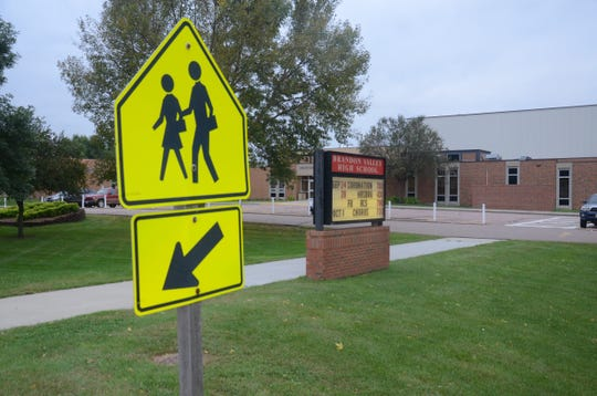 Crosswalks near schools are clearly marked with yellow signage depicting people walking, which drivers should pay attention to.