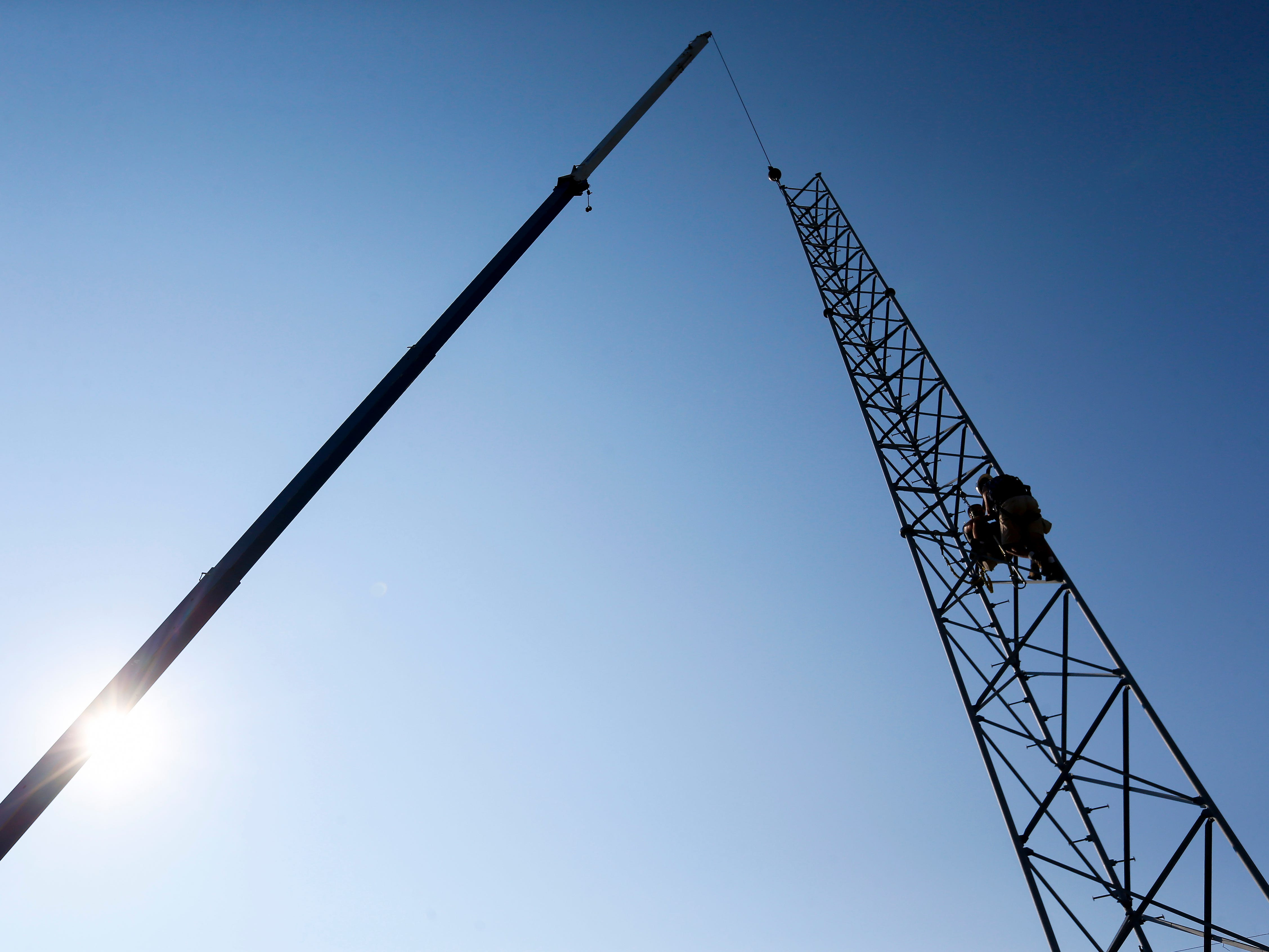 Craig House, left, and Tim Sloan, both of DIY Broadband, disassemble an old pager tower on Thursday, Sep. 20, 2018. The tower was located on property just purchased by Arnie's Plumbing, Heating and Air Services near the intersection of Chase Street and Lyon Avenue.