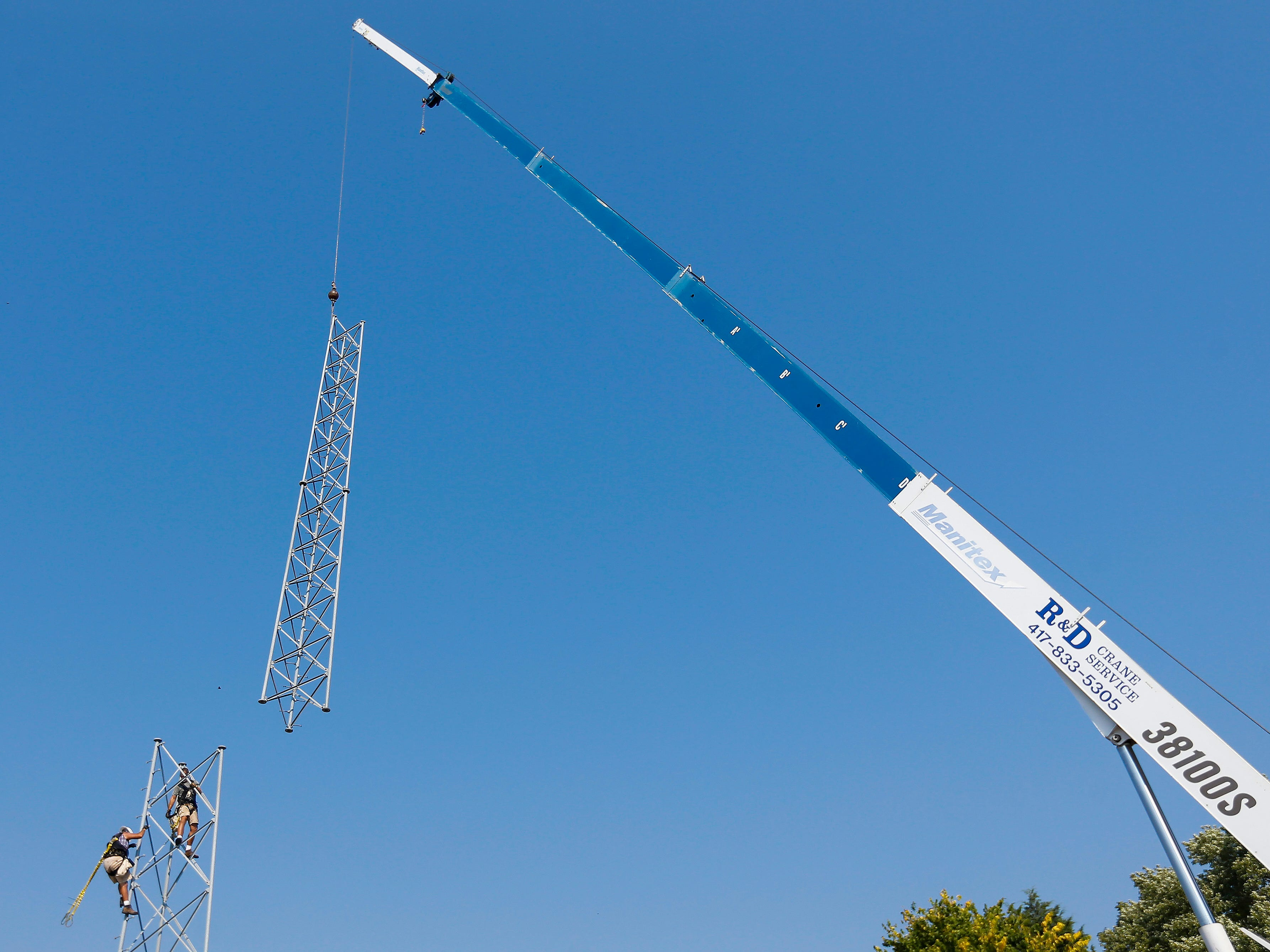Craig House, right, and Tim Sloan, both of DIY Broadband, watch as a 40-foot section of an old pager tower in Springfield is lowered to the ground on Thursday, Sep. 20, 2018. The tower was located on property just purchased by Arnie's Plumbing, Heating and Air Services near the intersection of Chase Street and Lyon Avenue.