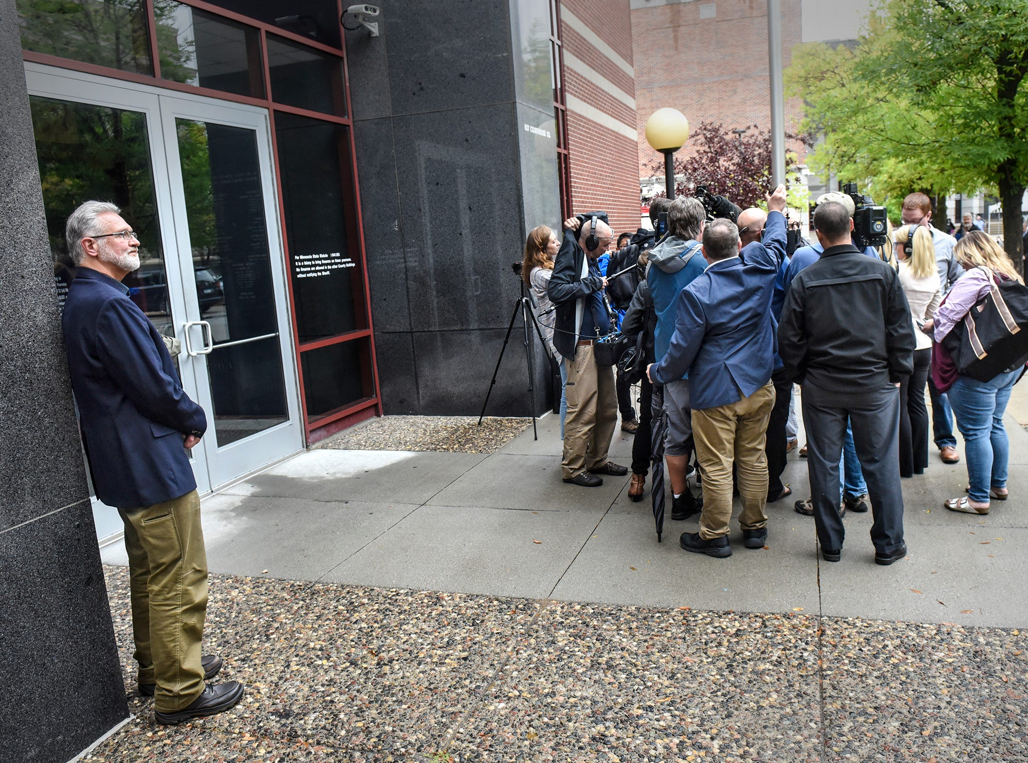 Jerry Wetterling stands alone as reporters circle around former FBI agent Al Garber following a press conference for the release of investigative files in the Jacob Wetterling case Thursday, Sept. 20, 2018, in St. Cloud. Wetterling was kidnapped and killed in 1989.