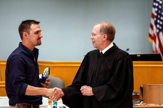 Brandon Jagodzinski shakes hands with Portage County Circuit Judge Thomas Flugaur during his graduation ceremony from the Portage County drug court in Stevens Point, Wis., Monday, Sept. 17, 2018.