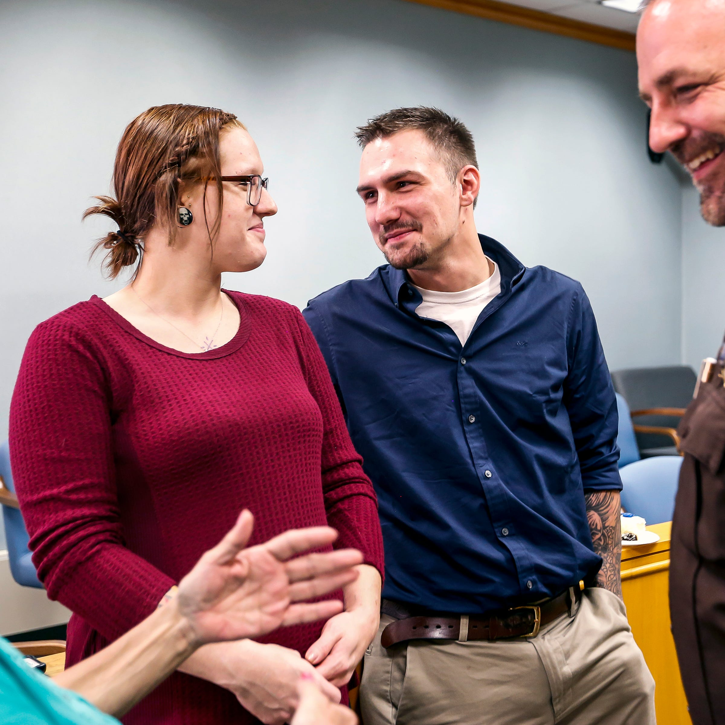 Brandon Jagodzinski and his fiance Kelsey Koehler mingle with family members, law enforcement officers, and other drug court participants, during his graduation ceremony from the Portage County drug court in Stevens Point, Wis., Monday, Sept. 17, 2018.