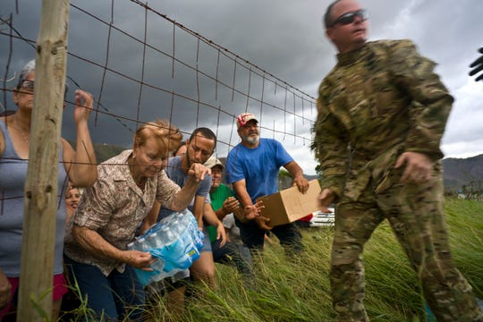 In this Oct. 7, 2017 file photo, a Puerto Rican National Guard delivers food and water brought by helicopter in the San Lorenzo neighborhood of Morovis, Puerto Rico, two weeks after Hurricane Maria hit. Puerto Rico was understocked in food and fresh water in part because Hurricane Irma struck two weeks before Maria, battering the U.S. Virgin Islands. Staff was depleted because of wildfires and other major natural disasters. (AP Photo/Ramon Espinosa, File)