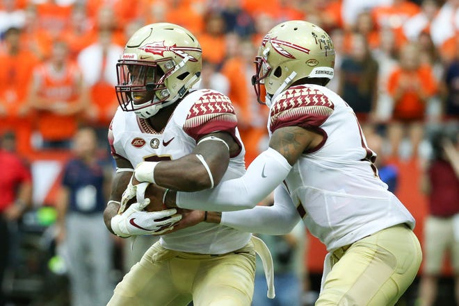Florida State Seminoles running back Cam Akers (L) takes a hand off from quarterback Deondre Francois (R) against the Syracuse Orange during the first quarter at the Carrier Dome.