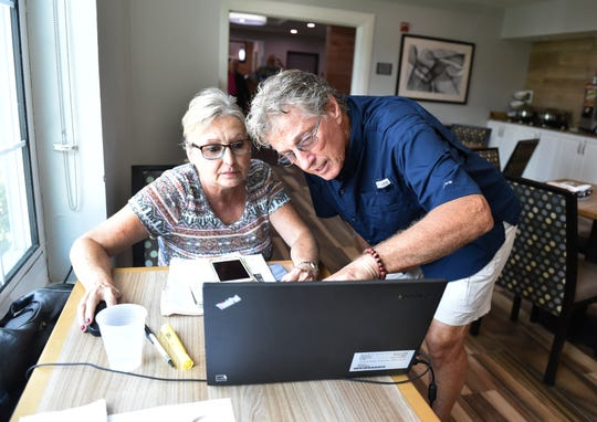 """Richard Knight (right), a resident at Castaway Cove neighborhood in Vero Beach, views his residence on a map as Patty Rawlings, of Arcadis, a consultancy firm from Orlando, helps comfort displaced residents like Knight as the U.S. Army Corp of Engineers searches somewhere in Knight's neighborhood for the remains of WW II-era munitions, on Thursday, Sept. 20, 2018, in Vero Beach. """"They can come spend the day at the hotel,"""" Rawlings said. """"They can use the facilities, use the pool, we have lunch scheduled for them, and we just try to make it as easy as an experience as possible."""" Knight is one of about 25 residents temporarily staying inside the Country Inn & Suites lobby by the Outlet Mall at I-95, who have been asked to evacuate their homes as the Corps continues to search for possible munitions left behind from training exercises during the war. """"It's a little bit nerve racking, but I hope they don't find anything,"""" Knight said."""