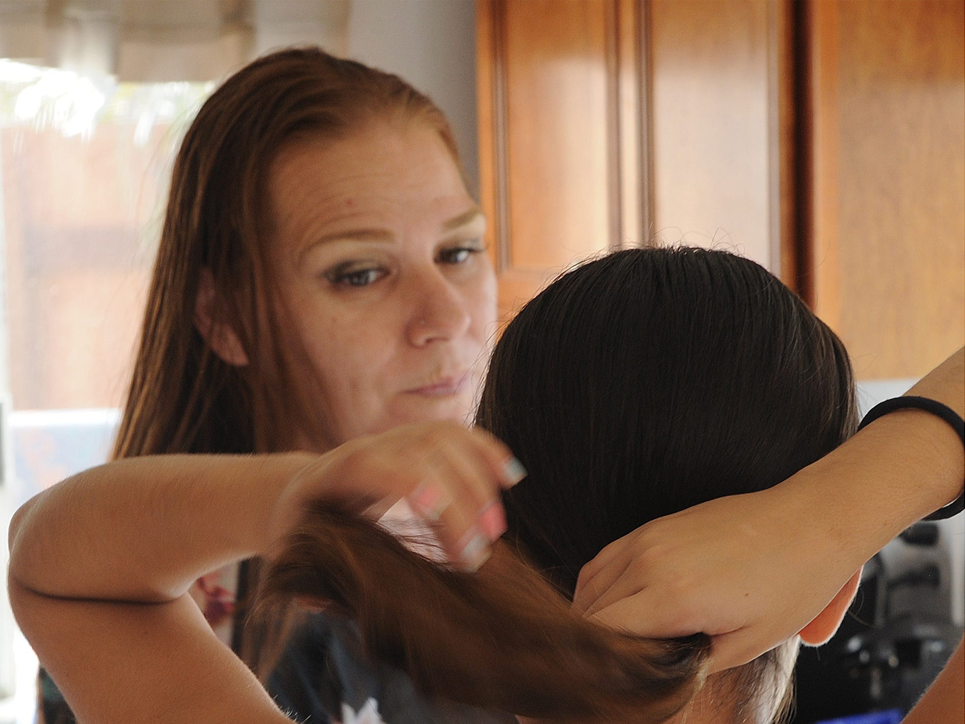 Sabrina Boyer talks to her foster daughter Angie as they prepare a cake in the Oxnard home they share. Boyer and Angie are part of an intensive services foster care program.