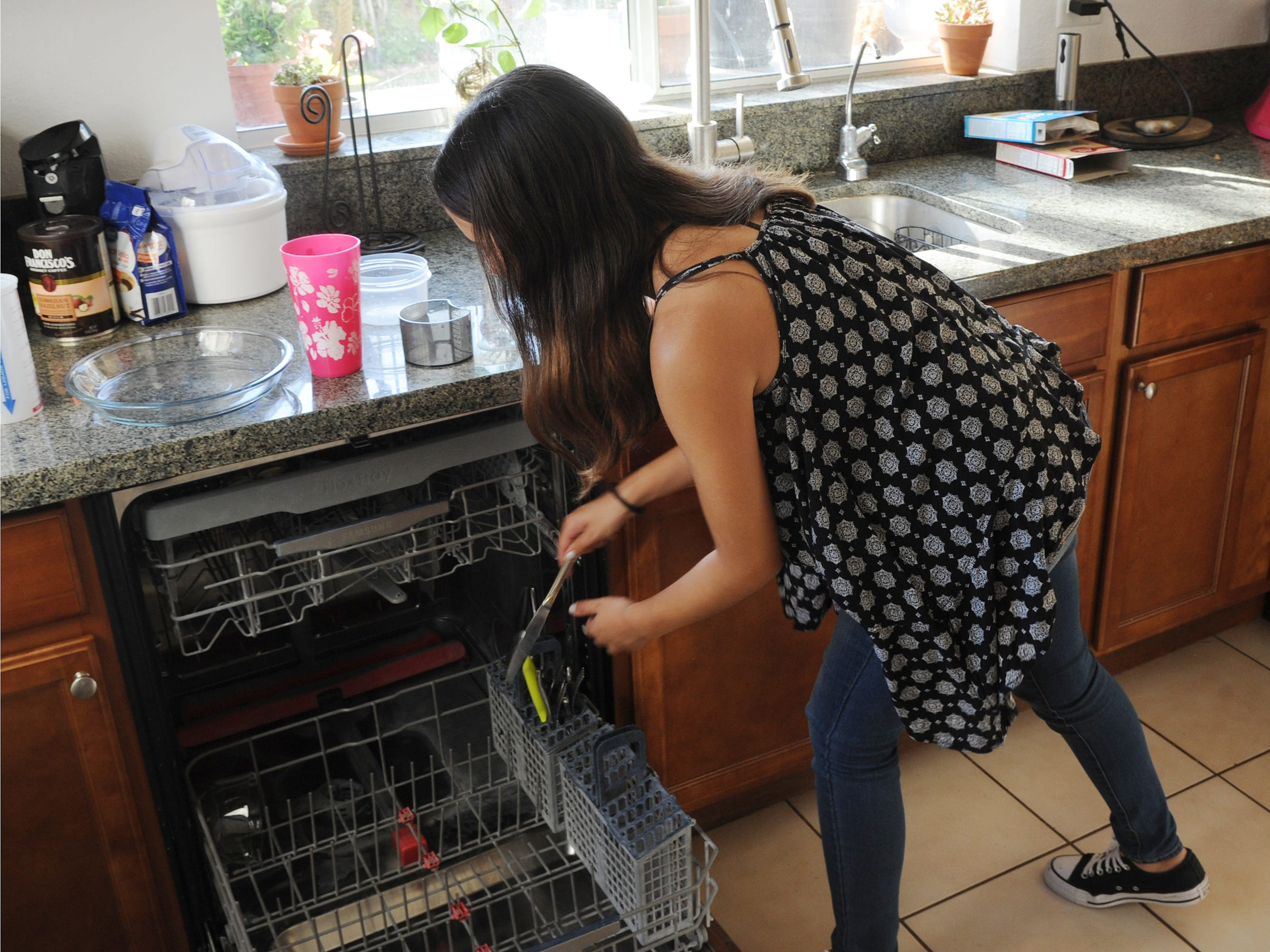 Angie works in the kitchen of the Oxnard home she shares with her foster mother.
