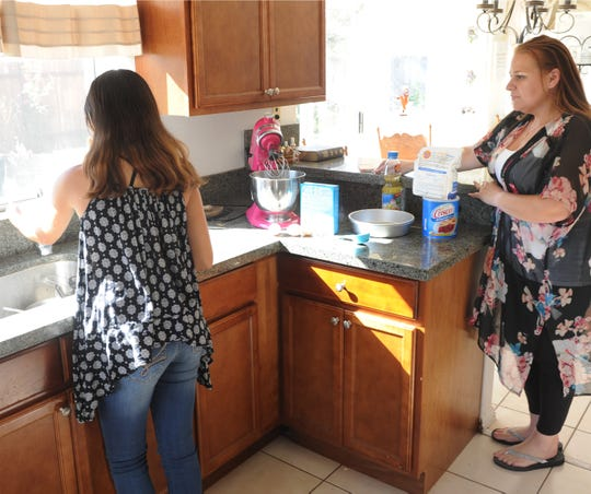 Sabrina Boyer and her foster daughter Angie prepare a cake in the kitchen of the Oxnard home they share.