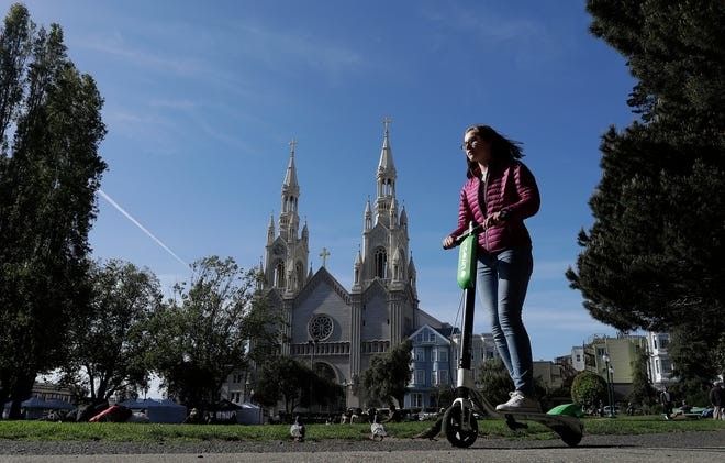 In this April 17 photo, a woman rides a motorized scooter in Washington Square Park in San Francisco. Gov. Jerry Brown signed legislation requiring helmets only for people under age 18 while riding motorized scooters.