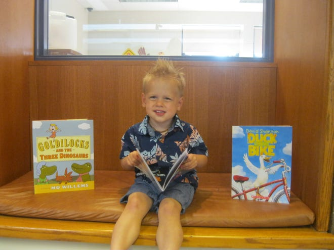 Logan Fisher of Millville poses with the prize books he received for being the top reader during Vineland Public Library's Summer Reading Program. Book prizes were funded by The Friends of the Vineland Public Library.