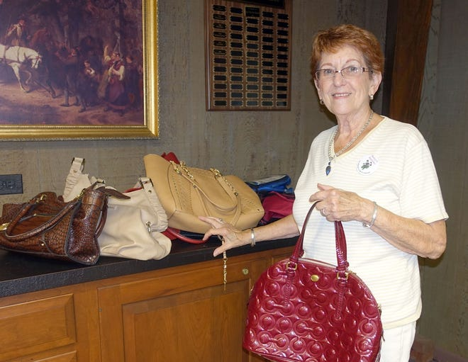 "Nancy Steelman, a member of the Woman's Club of Vineland, shows off some of the handbags donated by club members to be shared with the Boys & Girls Club of Vineland for its ""bags of beauty"" project."