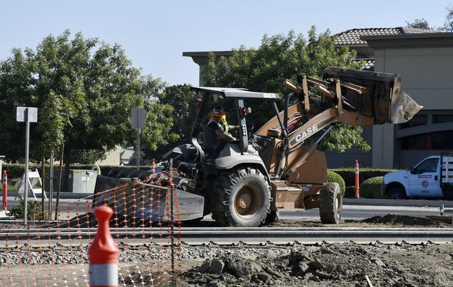 Crews work at the intersection of Goshen Avenue and Demaree Street on Wednesday, September 19, 2018.