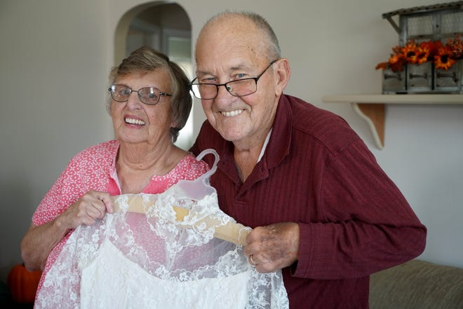 Betty Jean, 81, and Charles, 85, Morrison, hold her 1957 wedding dress. They will remarry Saturday, Sept. 22, because their original license has been lost.