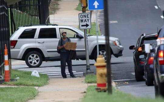 A man holds sign up while soliciting vehicles along South Adams Street in Wilmington.
