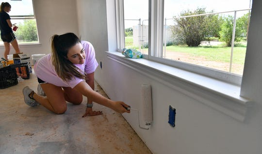 Whitney Taylor and other members of the Midwestern State University women's basketball team volunteered to paint a Habitat for Humanity home on Dallas Street Thursday.