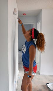Kityana Diaz helps paint part of a Habitat for Humanity home Thursday afternoon. Diaz and other members of the Midwestern State University women's basketball team volunteered.