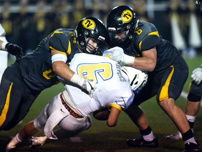 Tri-Valley's Garrett French, left, and Greg Nolder bring down Philo's Casey Munyan during the Scotties' 31-10 victory over the Electrics last season.
