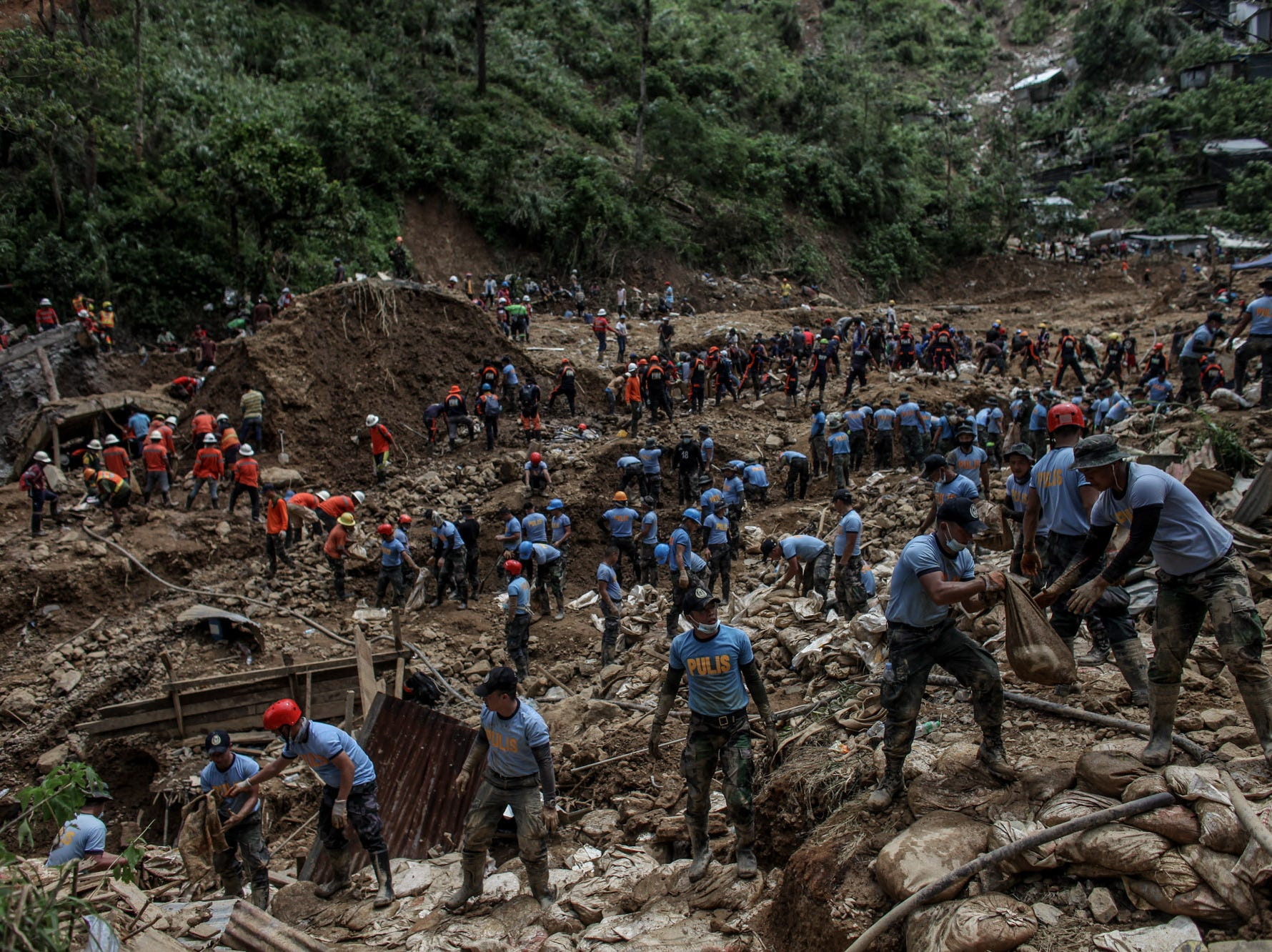 Filipino rescuers dig at the site where people were believed to have been buried by a landslide on Sept. 19, 2018 in Itogon, Benguet province, Philippines.
