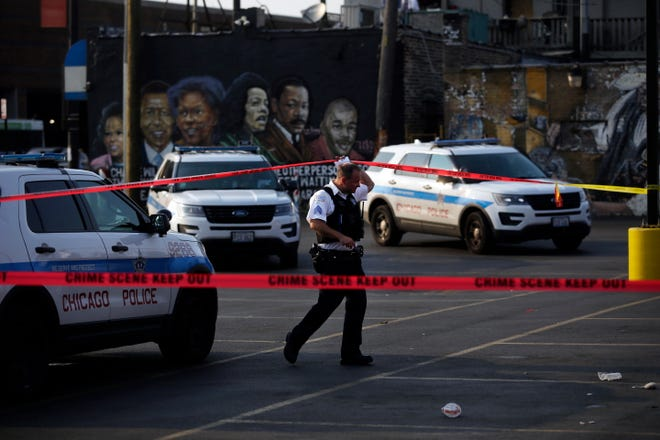 A Chicago Police officer works at the scene of a shooting on South Kedzie Avenue in August. Police arrested or identified a suspect in 15.4 percent of the 254 homicides committed in the city in the first half of 2018.