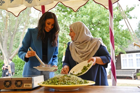 Duchess Meghan helps prepare green rice at the launch party for a cookbook by survivors of the Grenfell Tower fire, who formed a community kitchen after the 2017 blaze left them with nowhere to prepare meals.