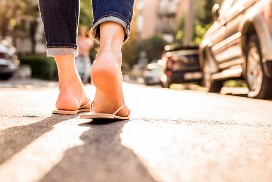 Woman Wearing Flipflops Walking Down The Street On A Sunny Summer Day Closeup Of The Feet