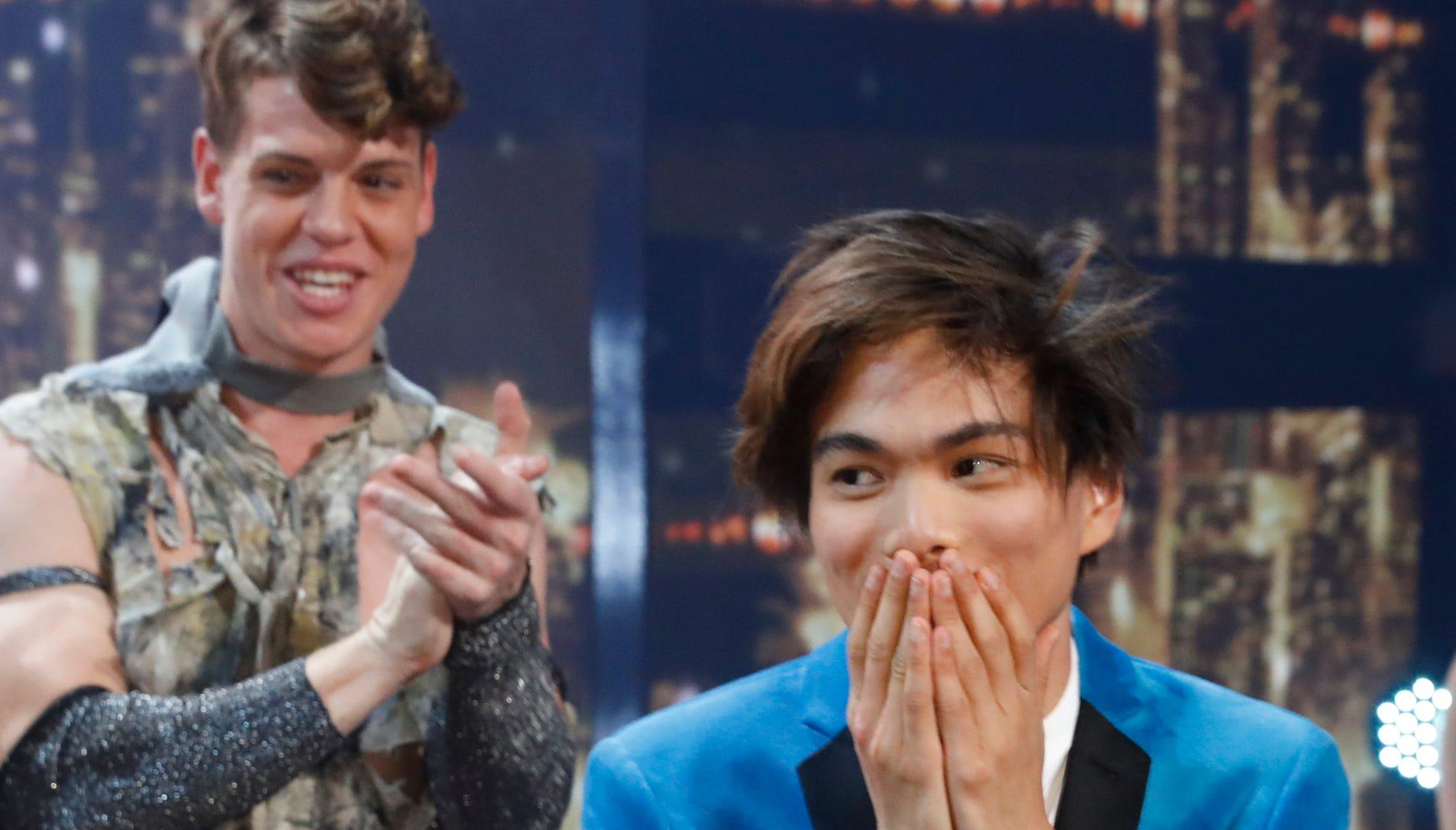 Magician Shin Lim, right, absorbs being named the winner of 'America's Got Talent' as a member of runner-up Zurcaroh, a dance group, applauds behind him.