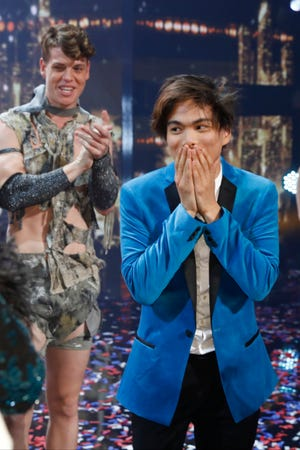 Magician Shin Lim, right, absorbs being named the winner of 'America's Got Talent' as a member of runner-up Zurcaroh, a dance group, applauds behind him.