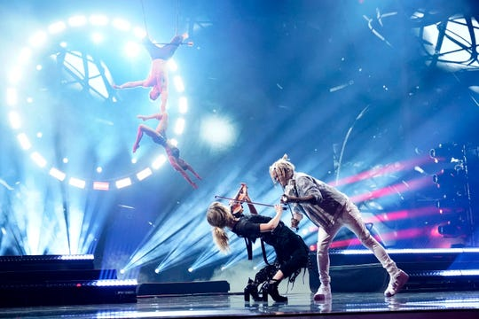 Contestant Brian King Joseph duels electric violins with Lindsey Stirling while Duo Transcend perform above in the