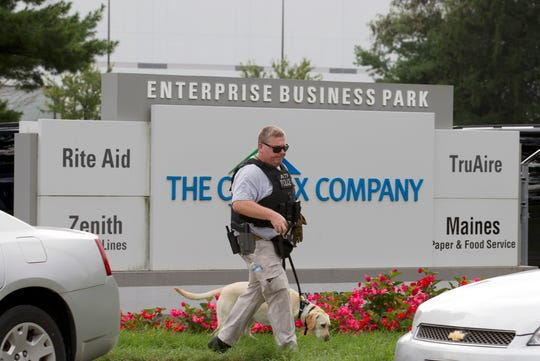 ATF police officer with a sniffing dog walks out of the industrial complex in Aberdeen, Maryland, on Sept. 20, 2018.