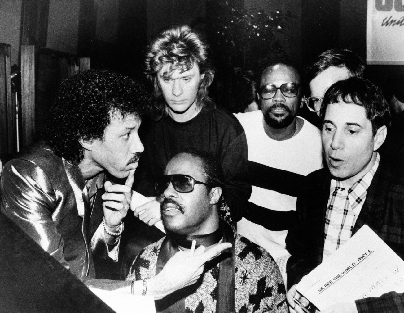 """This 1985 black and white file photo shows Lionel Richie, clockwise from left, Daryl Hall, Quincy Jones, Paul Simon and Stevie Wonder record """"We Are The World"""" by USA for Africa."""