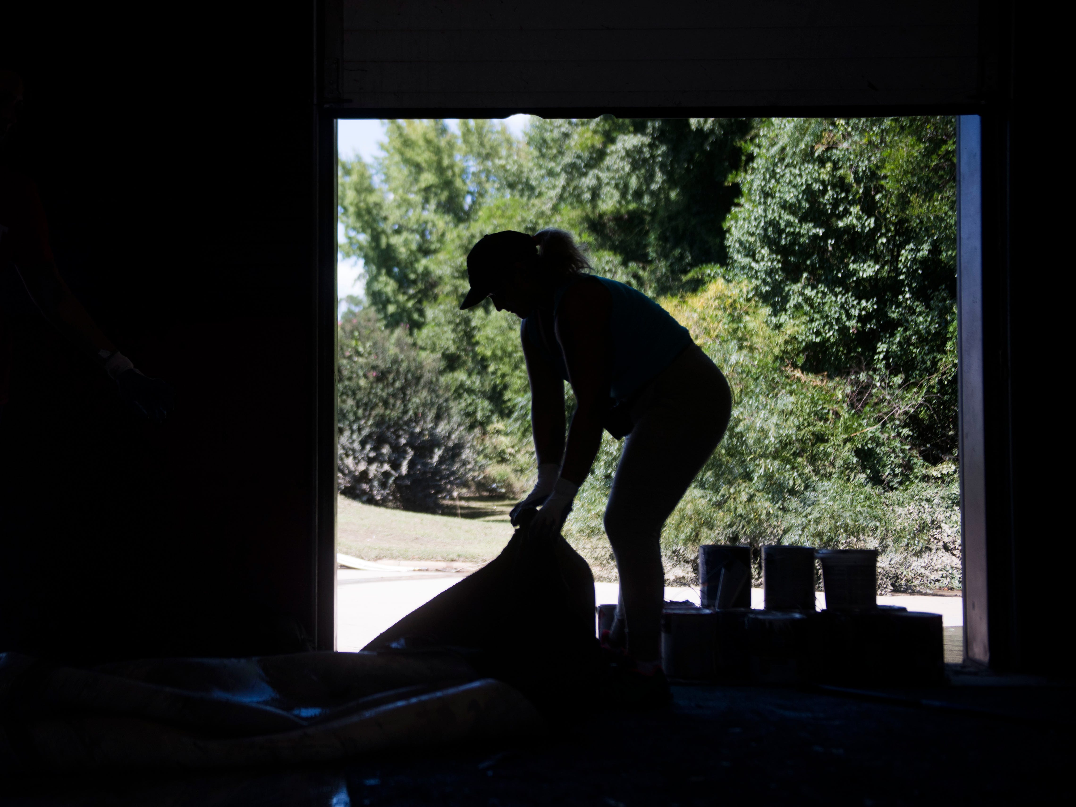Laura Burgos pulls up carpet at Evolution Athletics East, which was flooded by the Little River after Florence, in Spring Lake N.C.,Sept. 19, 2018.