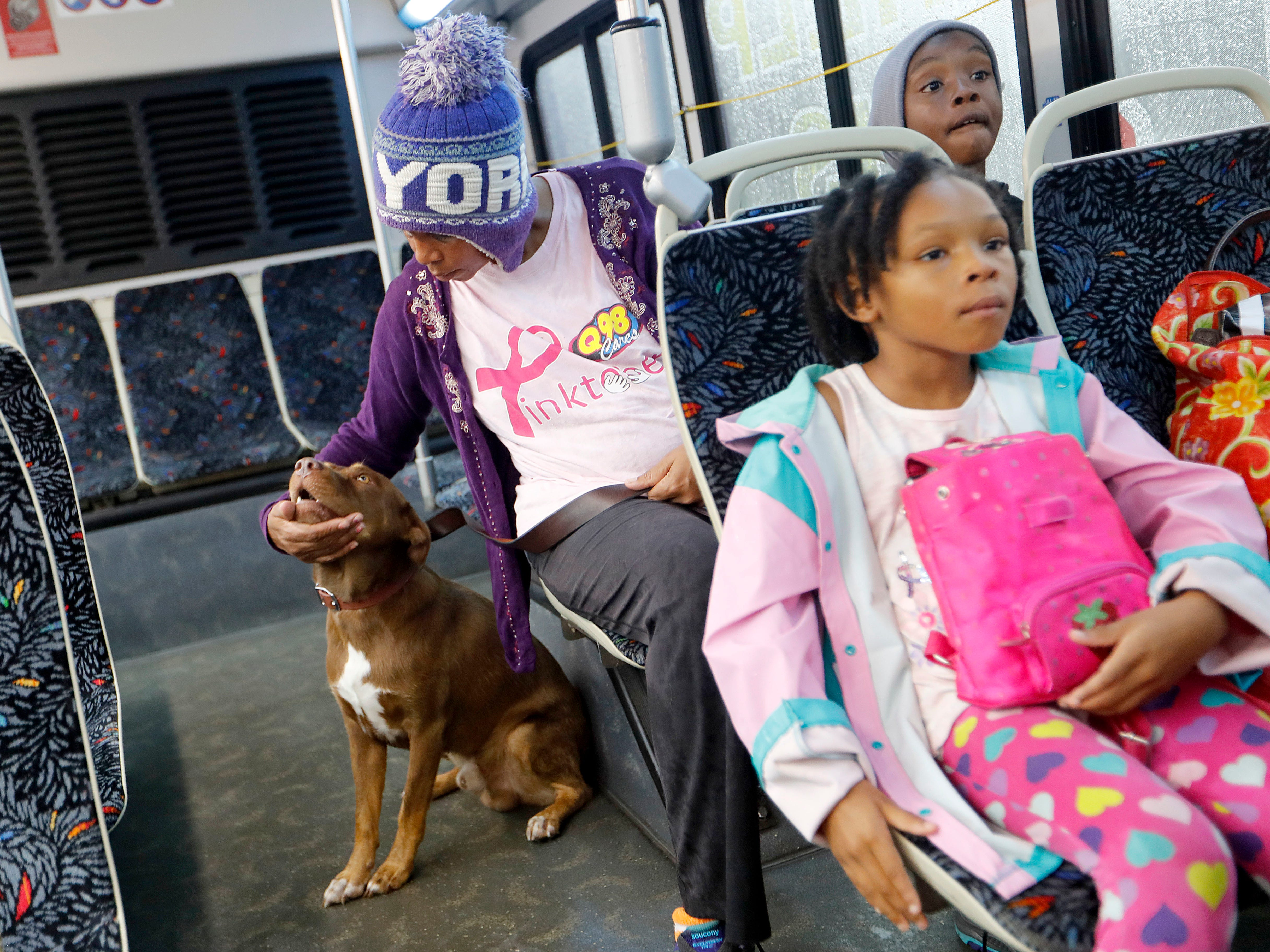 Dana Taylor, pets her dog Brownie after being evacuated with her children Dana 7, and Timothy, 9, right, from their flooded neighborhood as Florence continues to dump heavy rain in Fayetteville, N.C.,  Sept. 16, 2018.